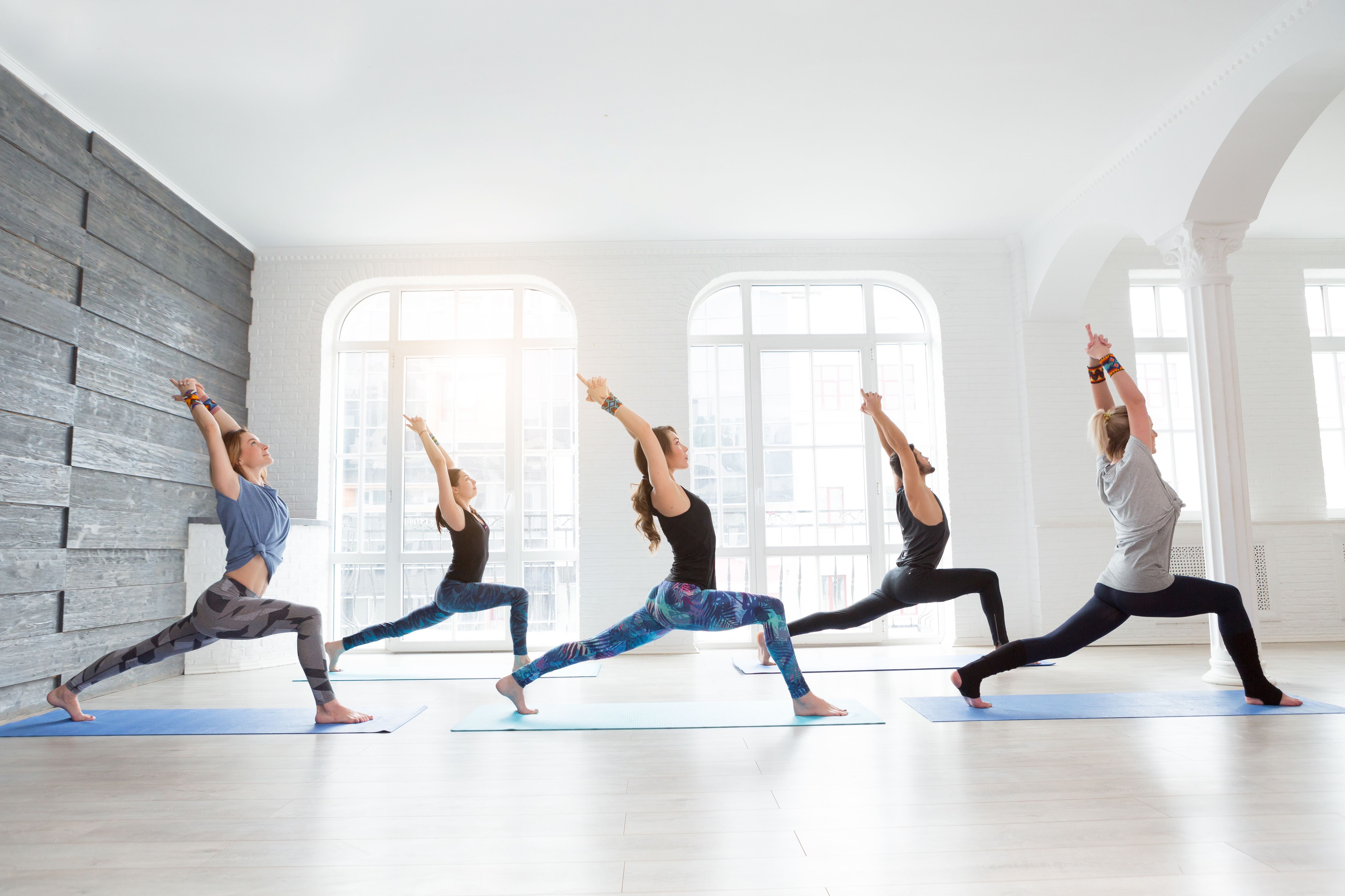 Group of people doing yoga warrior pose at white studio ...